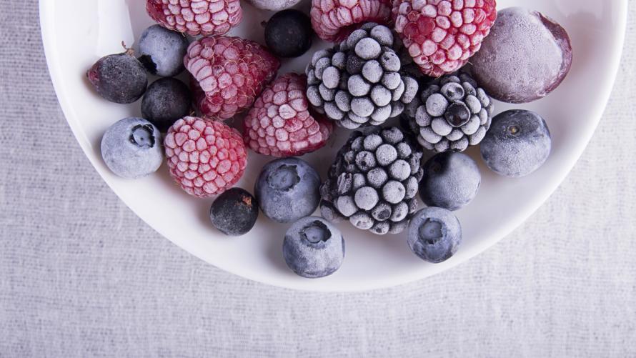 Gefrorene Beeren (Himbeeren, Brombeeren, Blaubeeren) auf weißem Teller