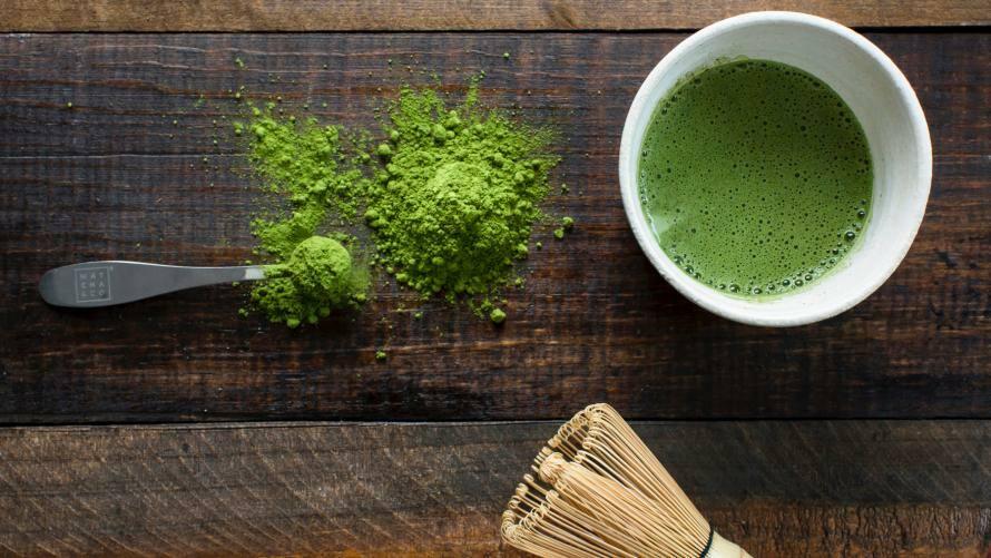 Matcha Tee in einer Tasse, daneben Matchabesen auf Holzuntergrund