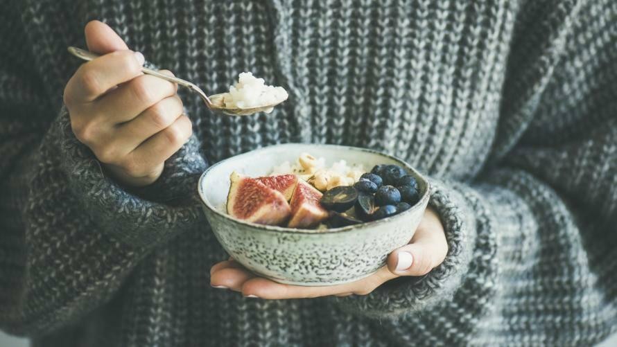 Frau mit Strickpulli hält Schüssel mit Frühstück